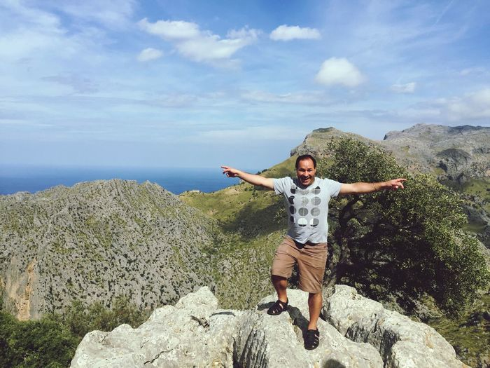 Portrait Of Man With Arms Outstretched Standing On Rocks Against Sky