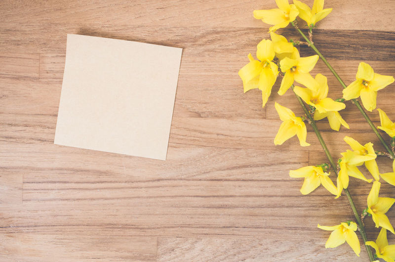 Blank adhesive note by yellow flowers on table