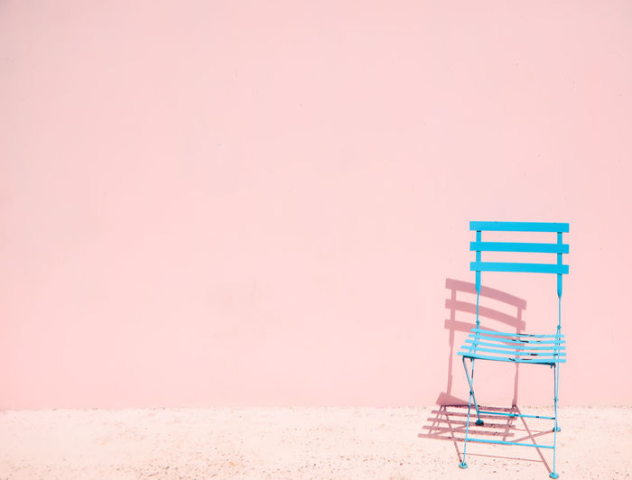 Empty chair against pink sky