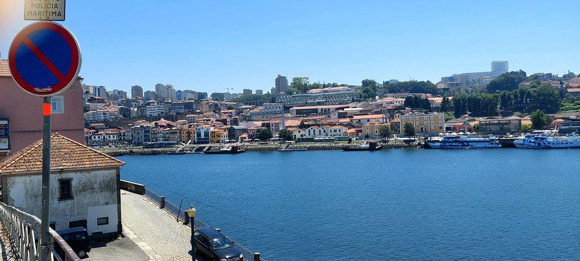Buildings by river against blue sky