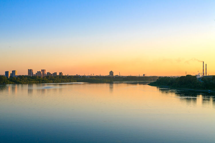 Sunset over the river Tom in Kemerovo city. River View Architecture Building Building Exterior Built Structure City Cityscape Clear Sky Copy Space Kemerovo Landscape No People Outdoors Reflection River Riverscape Siberia Sky Sunset Tranquility Urban Skyline Water Waterfront