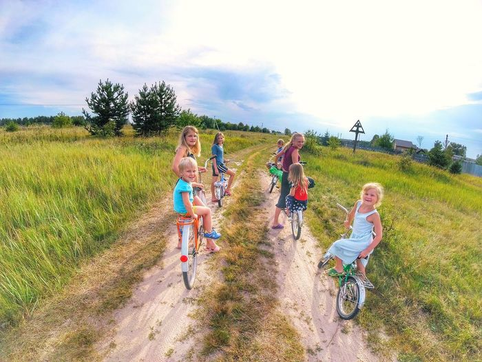 Family and friends riding bikes EyeEmNewHere Playing Boy Toddler  Kids Bysicle Riding Fun Summertime Bike Outdoor Countryside Village Family Siblings Summer Sports Young Women Sports Race Tree Rural Scene Togetherness Agriculture Field Cereal Plant Friendship Sky Cultivated Land Farm Cycling Agricultural Field