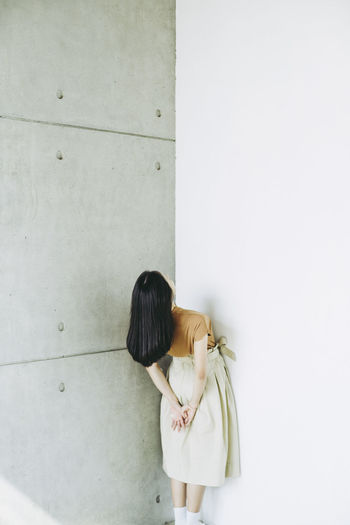 Woman bending against wall