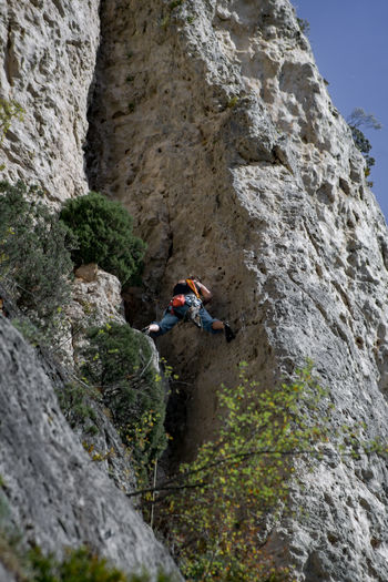 An athlete is climbing, high in the rocks through the sky and the nature in the Jonte Canyon in the region of Lozère in the South of France. Adult Adults Only Adventure Challenge Cliff Climbing Danger Day Extreme Sports Mountain One Man Only One Person One Young Man Only Only Men Outdoors People RISK Rock - Object Rock Climbing Rope Safety Skill  Sport Sports Helmet Strength