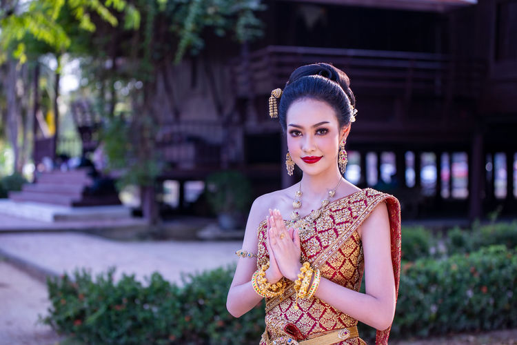 Portrait of beautiful young woman in traditional clothing standing with hands clasped outdoors
