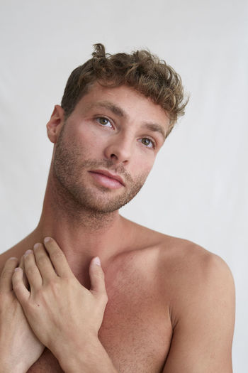Portrait of shirtless young man against white background