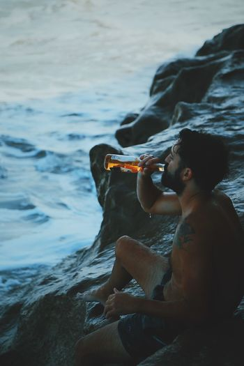 Side view of shirtless mid adult man drinking beer while sitting on rock formation