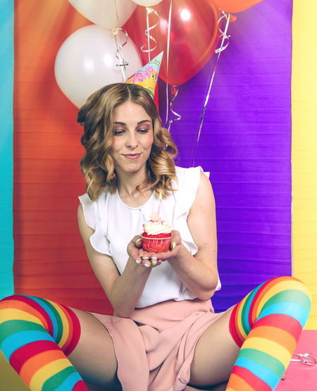 Portrait of smiling young woman holding colorful balloons