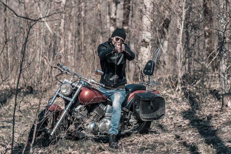 Full length of mid adult man sitting on motorcycle in forest