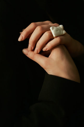 Close-up of woman holding hands over black background