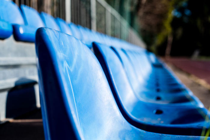 Blue chairs seats line in sports playground Chair LINE Bleachers Blue Close-up Day Ground No People Outdoors Playground Seats Selective Focus Sport ın A Row
