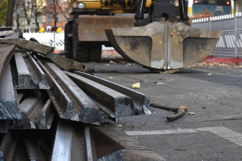 Pile of metal tracks lying on road at construction site