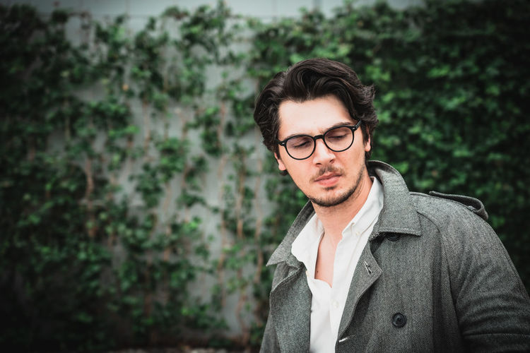 Man wearing eyeglasses standing against plants