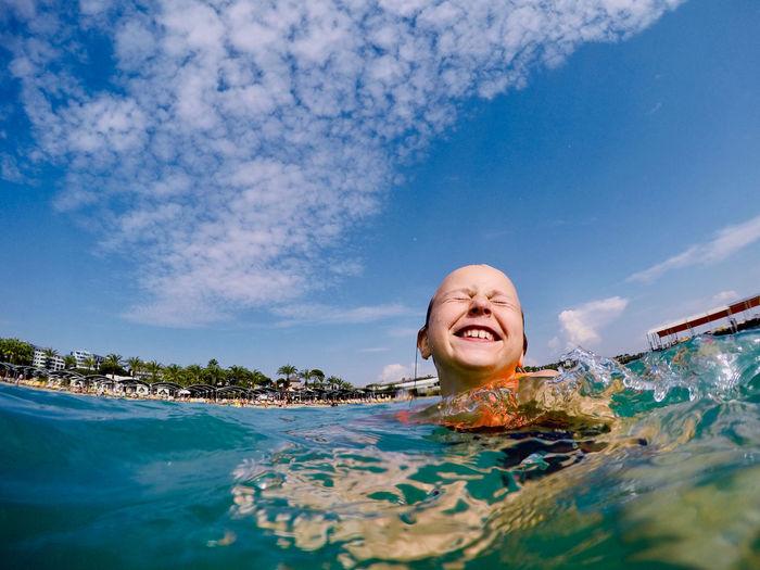 Smiling girl swimming in sea against sky
