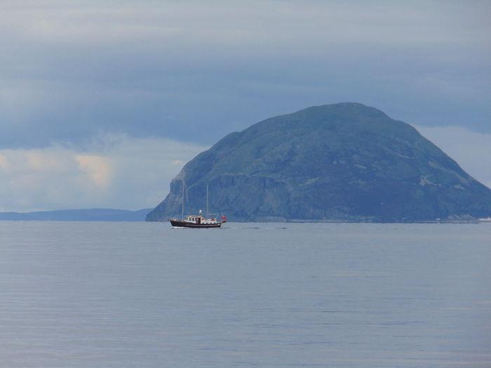 Sailboat sailing on sea against mountain