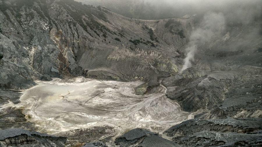 Hot spring emitting smoke by mountains