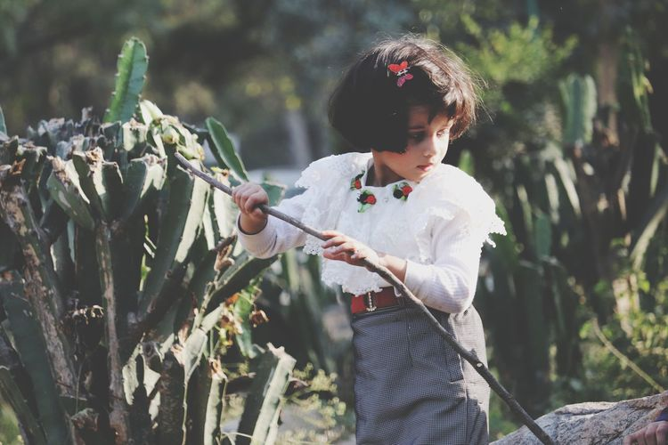 Girl holding stick while standing by plant