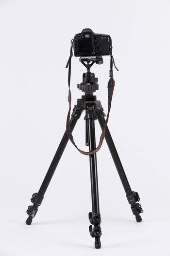 Camera Photography Multimedia Expertise Professional Occupation Tripod Photograph DSLR Lens Equipment Photographic Theme Photographing Black Nobody White Background SLR Camera Photography Themes Technology Studio Shot Camera - Photographic Equipment Photographic Equipment Indoors  Digital Camera Copy Space No People Activity Single Object Still Life Close-up