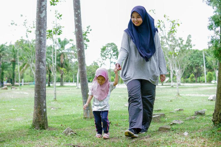 Full length of women standing on grass against trees