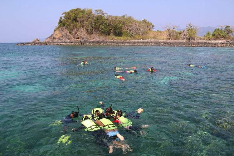 Tourists are snorkeling in the middle of the sea during the holidays Beauty In Nature Day Group Group Of People High Angle View Inflatable  Inflatable Raft Leisure Activity Lifestyles Medium Group Of People Men Nature Nautical Vessel Outdoors Real People Sea Transportation Water Waterfront Women