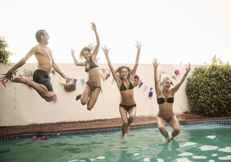 People enjoying in swimming pool against sky