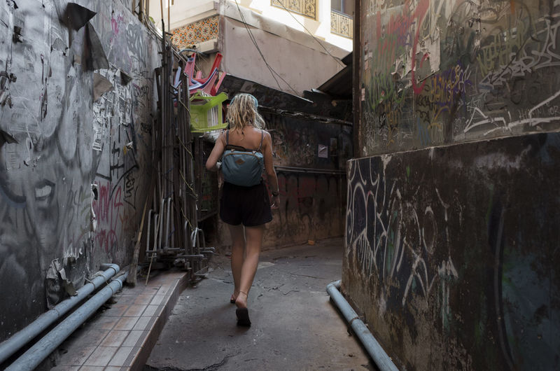 One Person Full Length Real People Rear View Young Adult Graffiti Architecture Young Women Standing Women Built Structure Lifestyles Casual Clothing Hair Adult Day Abandoned Indoors  Wall - Building Feature Hairstyle Deterioration