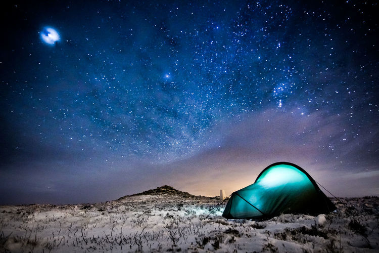 Illuminated Tent On Snow Covered Field At Night