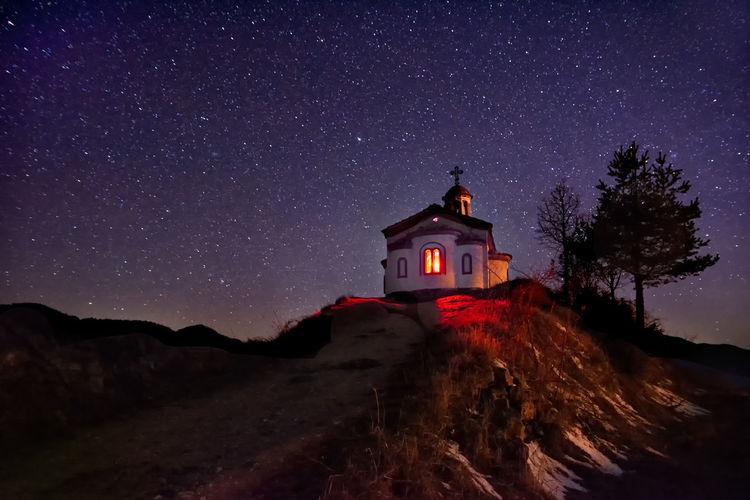 Illuminated building against sky at night
