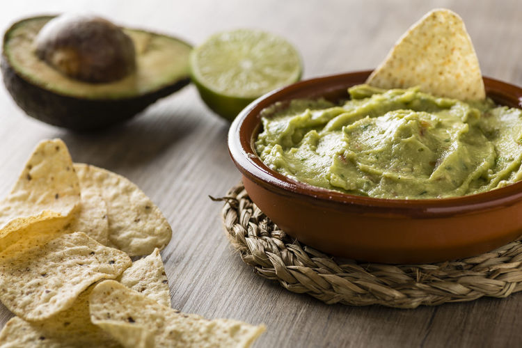 Tortilla chips with avocado on table