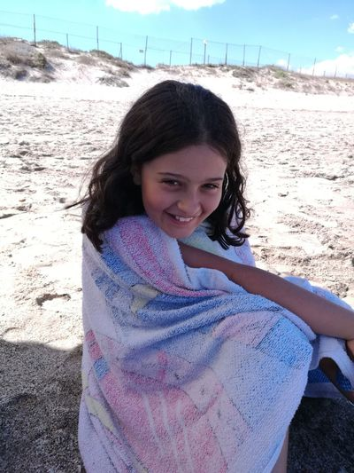 Portrait Of Smiling Girl Wrapped In Towel While Sitting On Sand At Beach