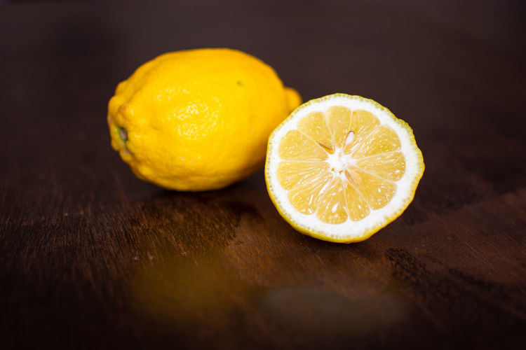 Antioxidant Citrus Fruit Close-up Cross Section Food Food And Drink Freshness Fruit Halved Healthy Eating Indoors  Lemon No People Orange Ripe Selective Focus SLICE Sour Taste Still Life Studio Shot Table Wellbeing Wood - Material Wood Grain Yellow