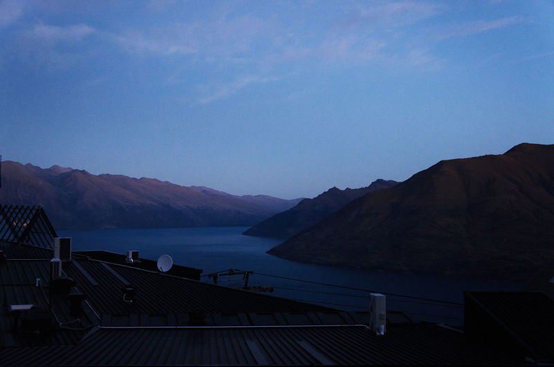 Scenic view of river and mountains against sky at dusk