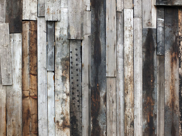 Rough textured timber wall made of stained mismatched recycled old planks