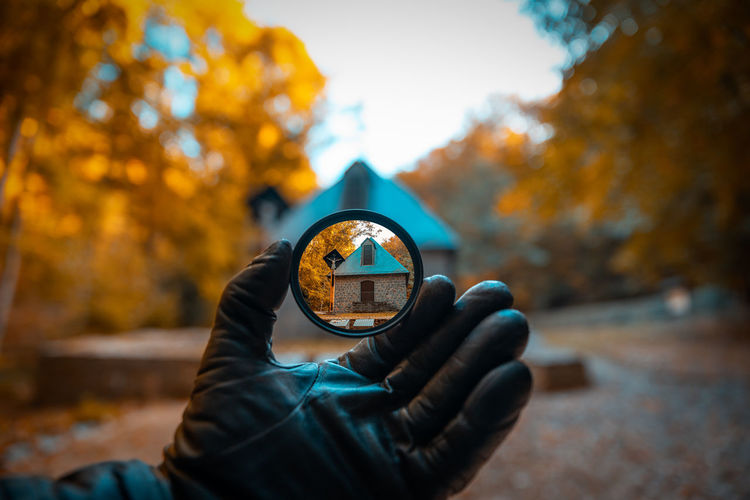 House seen through circle shaped glass held by hand