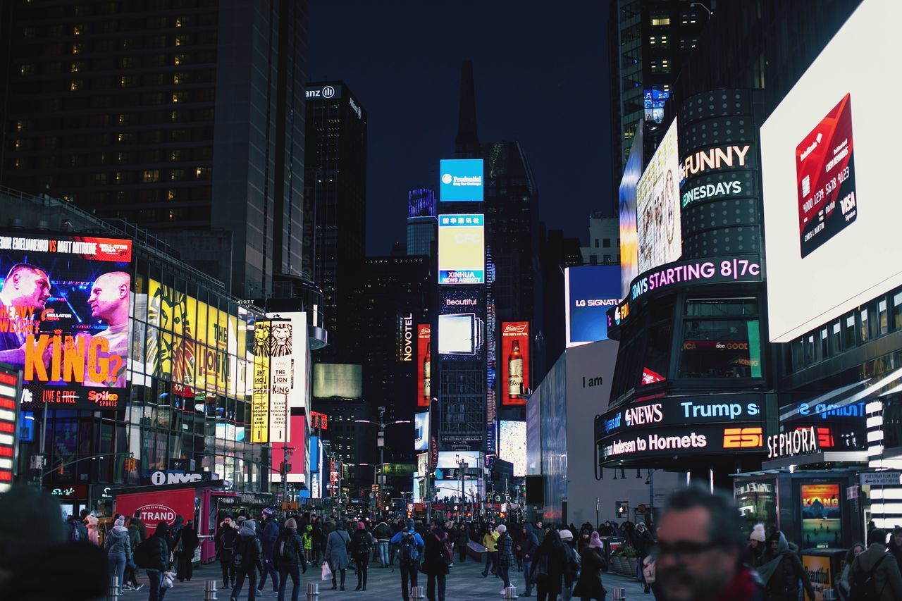 building exterior, architecture, city, built structure, large group of people, advertisement, modern, communication, illuminated, night, skyscraper, city life, outdoors, real people, crowd, travel destinations, women, men, cityscape, neon, urban skyline, people