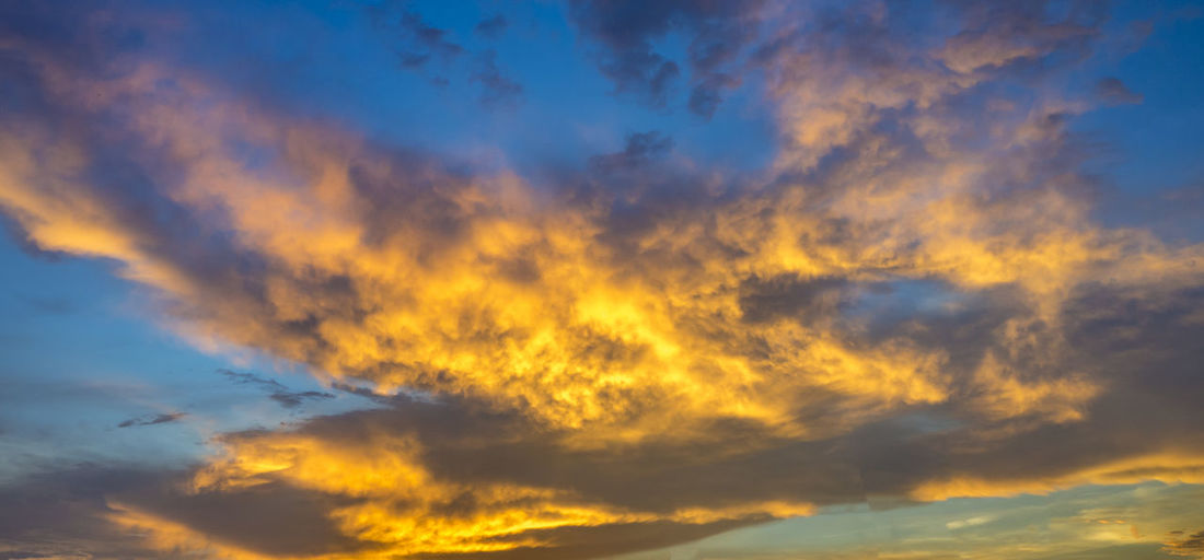 Sky Cloud - Sky Dramatic Sky Cloudscape Sunset Scenics - Nature Nature Beauty In Nature Blue No People Backgrounds Moody Sky Tranquility Orange Color Environment Yellow Low Angle View Atmosphere Wind Outdoors Abstract Meteorology Abstract Backgrounds Dark
