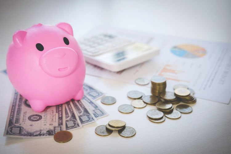 Close-Up Of Piggybank With Currency On Table