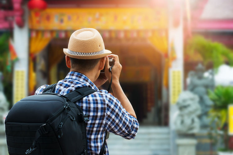 Rear view of man photographing temple through camera