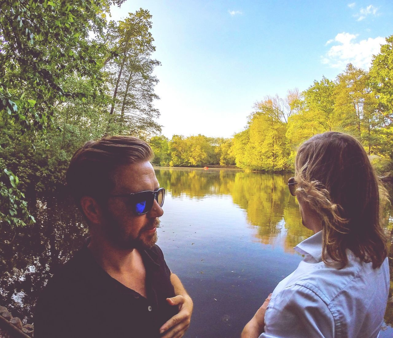 Friends Standing By Lake In Forest Against Sky