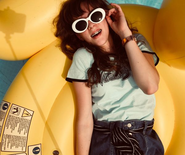 Portrait of smiling teenage girl wearing sunglasses while lying on raft in pool