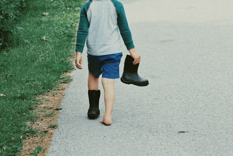 Rear view of boy holding rubber boot while walking on road
