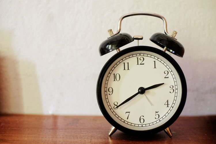 Close-up of alarm clock on table against wall
