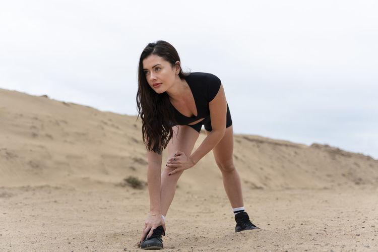 Full length of woman exercising on land against sky