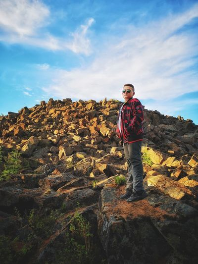 Full length of young man standing on rock against sky