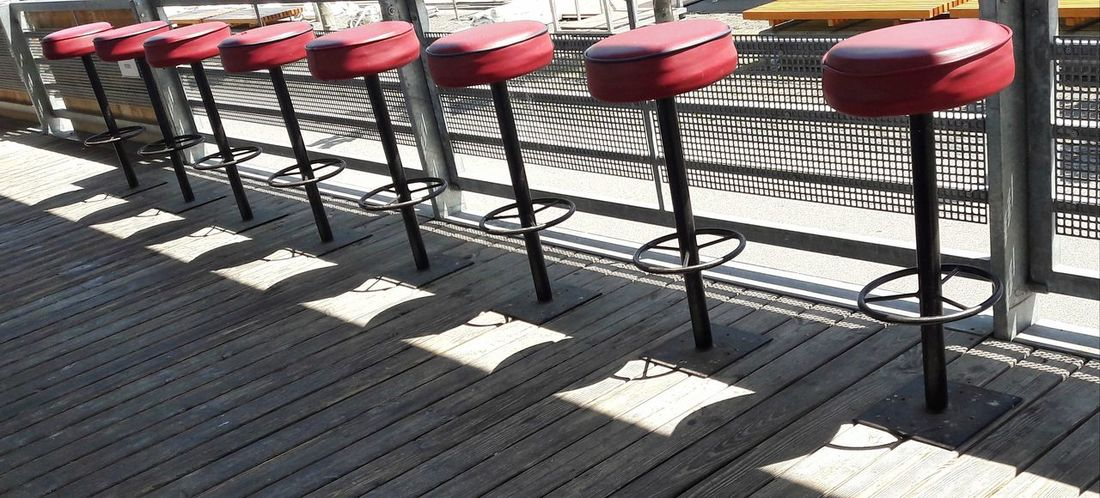 Party Location Bar Stools In A Row Street Bar Street Cafe Red Street Restaurant No People Empty Patterns Shadows Bar Stools Chair Pattern, Texture, Shape And Form Wood - Material Summertime Outdoors Day Open Air Row Of Seats Red Color Geometric Shapes Row Of Things Group Of Chairs Sunlight Shadow The Graphic City