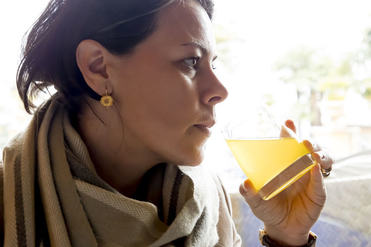 Woman Drinking Orange Juice Profile Backlit Beautiful Woman Close-up Contemplation Day Drinking Focus On Foreground Hairstyle Headshot Holding Leisure Activity Lifestyles Looking Looking Away One Person Orange Juice  Portrait Real People Scarf Side View Women Yellow Color Young Adult Young Women
