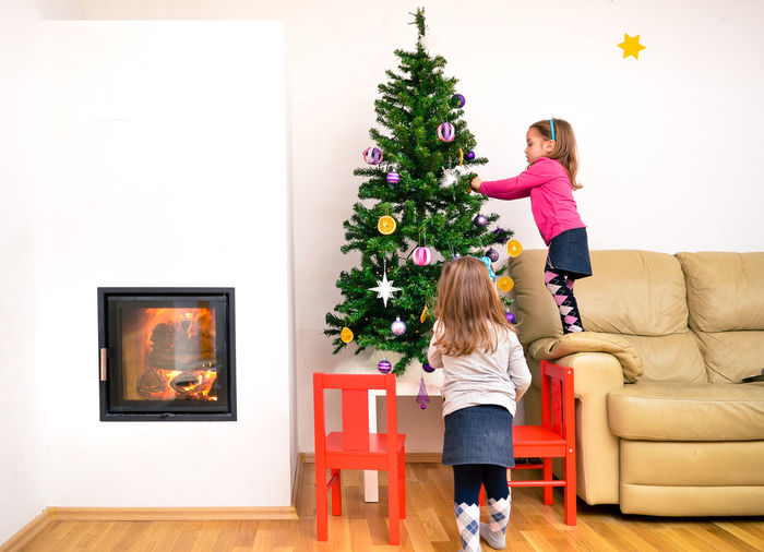 Rear view of girl with christmas tree at home