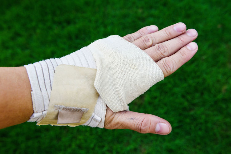 Cropped Image Of Person With Broken Hand Over Grassy Field