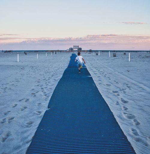 Rear view of boy running on blue carpet at jones beach