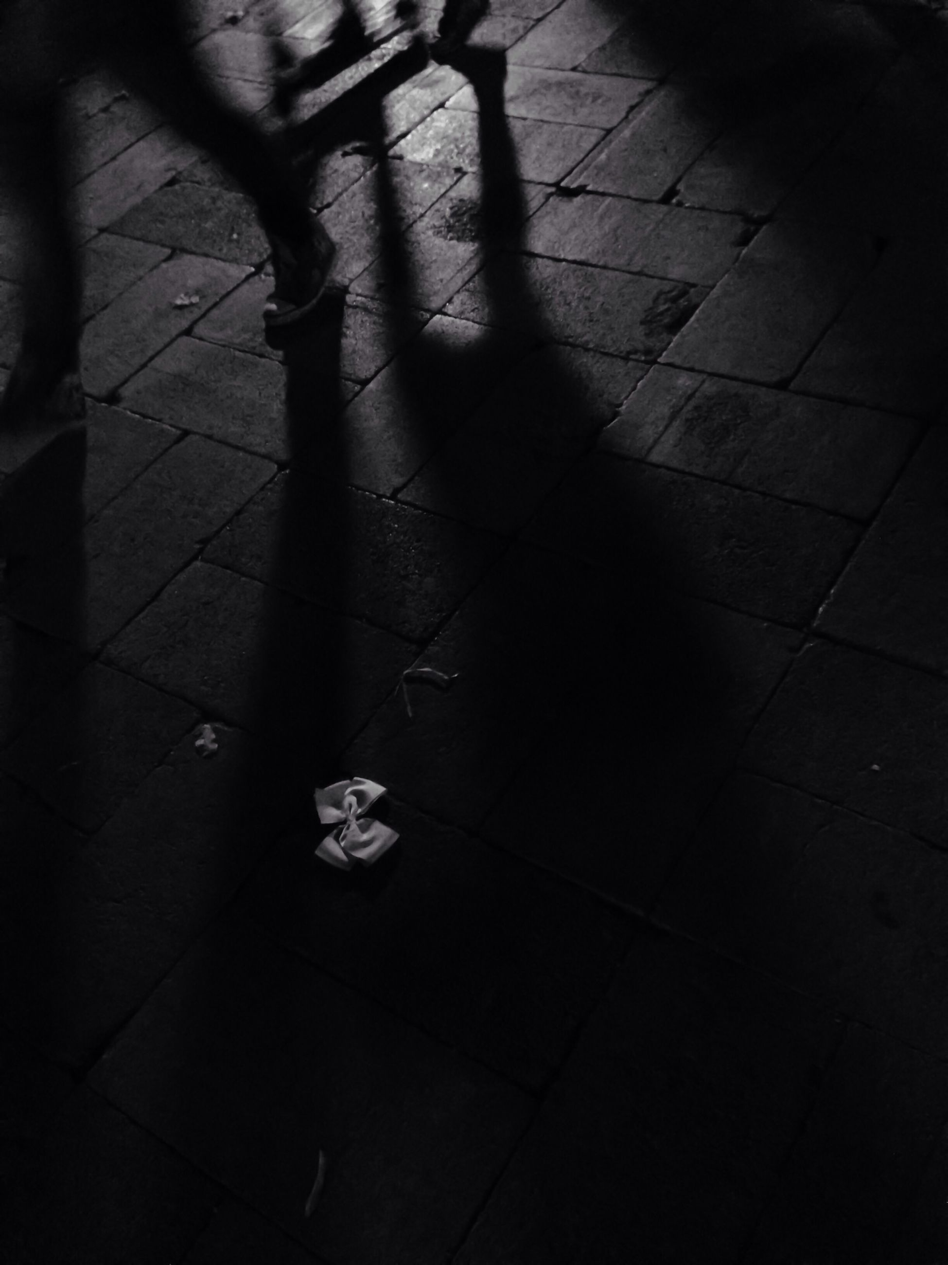 shadow, low section, high angle view, person, focus on shadow, sunlight, lifestyles, walking, street, tiled floor, unrecognizable person, men, leisure activity, standing, silhouette, sidewalk, footpath